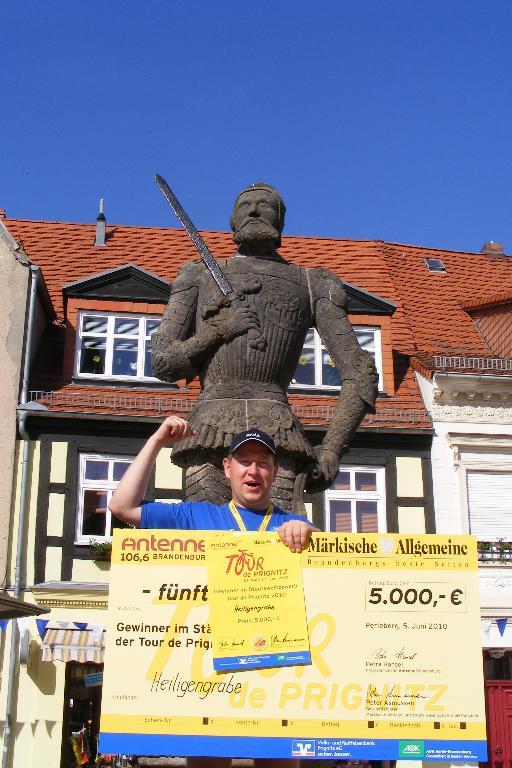 Gewinner Holger Kippenhahn - Bürgermeister Heiligengrabe - posiert mit dem Siegerscheck vor dem Roland auf dem Perleberger Marktplatz