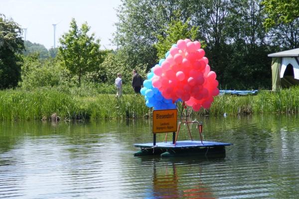 Mit Helium gefüllte Luftballons und Dorfeingangsschild auf dem Dorfteich im Pausenort Blesendorf 2010