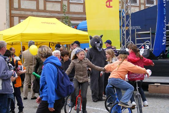 Pritzwalker Wappenwolf hinter Mädchen auf Einrädern auf dem Wusterhausener Marktplatz nach Etappe 3 der Tour-de-Prignitz 2010 von Pritzwalk nach Wusterhausen