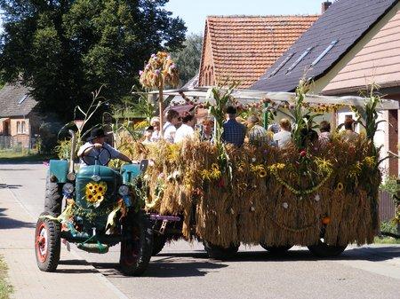 Bunt-geschmueckter-Traktor-mit-grossem-und-kleinen-Anhaenger faehrt-auf-die-Strasse-in-Maulbeerwalde